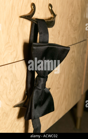 Bow tie hanging from drawer - Stock Photo