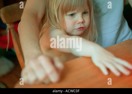 Frustrated girl sitting at table - Stock Photo
