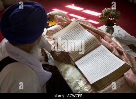 Sikh priest reading scripture Delhi India - Stock Photo