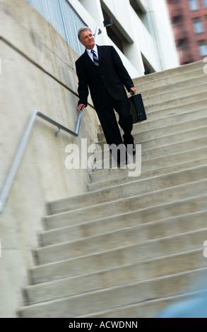 Businessman walking down stairs - Stock Photo