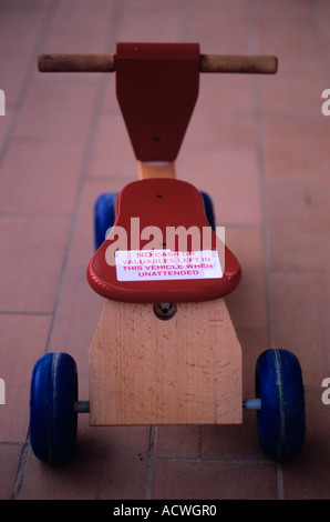 a toddlers trike or bicycle with a funny sticker on the seat no tools or equipment left in this vehicle overnight - Stock Photo