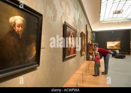 Visitors at the Rijksmuseum in Amsterdam viewing works by Rembrandt van Rijn The Netherlands - Stock Photo