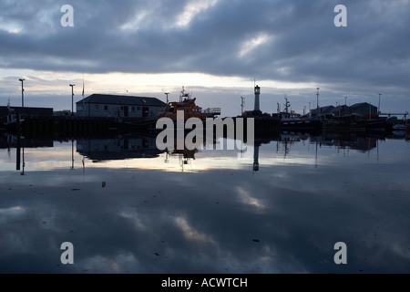 Kirkwall Harbour Orkney Scotland Lifeboat and Fishing boats and buildings reflected in Kirkwall Harbour at night - Stock Photo