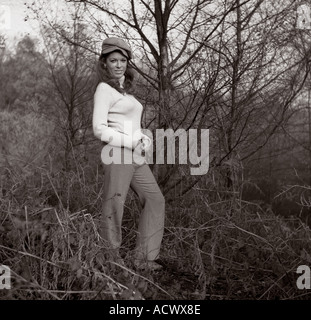 Young lady in 1970 s style clothing in winter woodland - Stock Photo