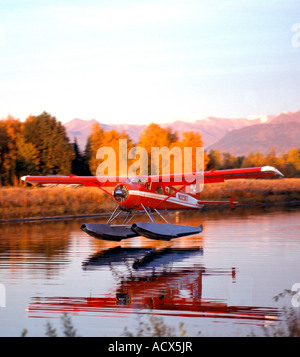 A Beaver floatplane is just about to touch down on Lake Hood Seaplane Base in Anchorage Alaska - Stock Photo