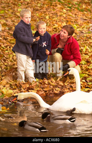A MOTHERS WALKS HER TWO CHILDREN IN A PARK - Stock Photo