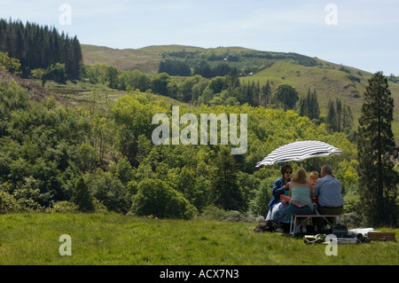 Summer holiday : Family under parasol in the shade picnicking in the sunshine on the Hafod Estate Pontrhydygroes - Stock Photo