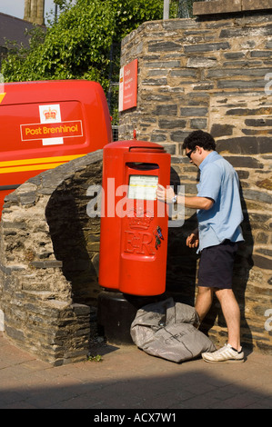 Postman collecting emptying the mail post from a post box outside Cardigan postal depot wales (logo in welsh on - Stock Photo