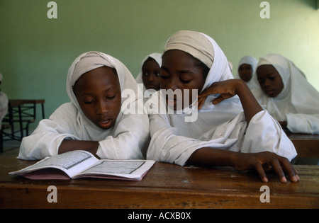 NIGERIA West Africa Kano Muslim girls in a primary school reading from a textbook sitting at desk in Islamic classroom - Stock Photo