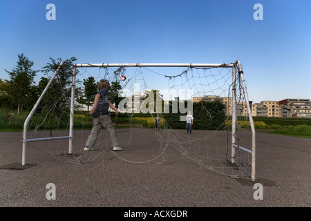Young boys playing football in Thames Barrier Park The goal nets are badly damaged - Stock Photo