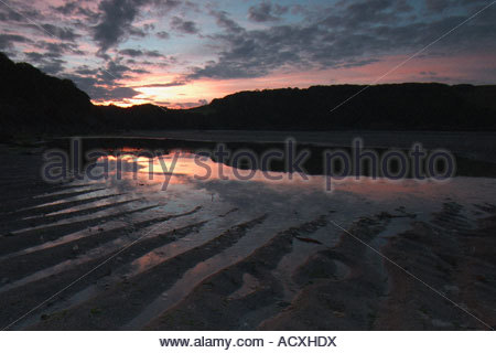 the sunrise reflecting off of the ripples in the sand of the river Erme in South Hams area of Devon - Stock Photo