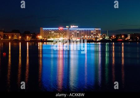 View across the Daugava river to Radisson SAS Daugava Hotel in Riga at night, Latvia - Stock Photo