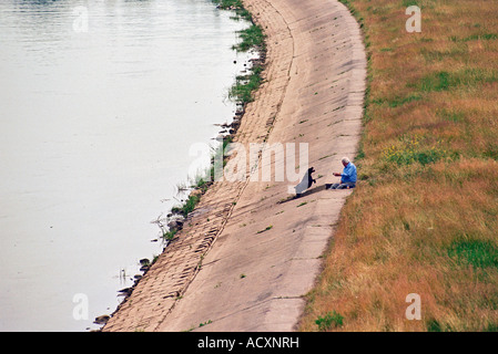 Man playing with his dog at the Warta river in Poznan, Poland - Stock Photo