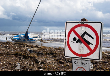 Shipwreck sailboat and no swimming sign due to high levels of water pollution after winter storm, Santa Barbara, - Stock Photo