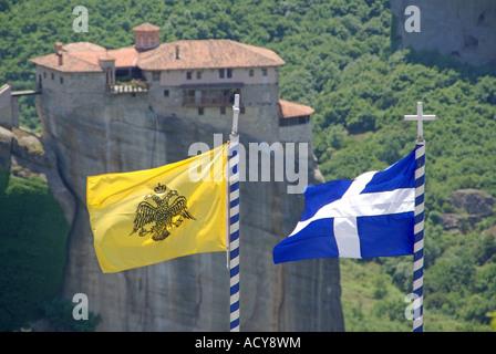 Greek national & Greek Orthodox church flag flying on hilltop monastery views across to similar monastery on rock - Stock Photo