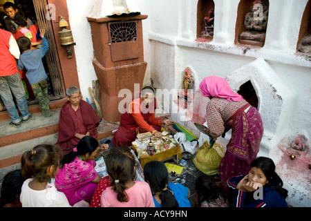 Family making a puja ceremony.Ajima Shrine.Bodhnath Stupa.Kathmandu Valley.Nepal - Stock Photo