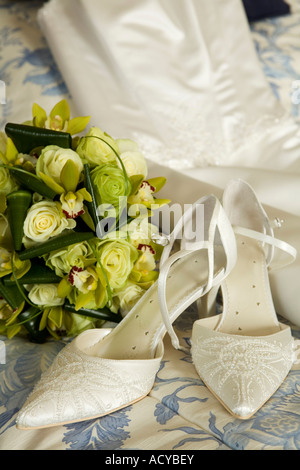 Ivory coloured brides wedding shoes laying on bed in front of bouquet of roses and diffused wedding dress. Space - Stock Photo