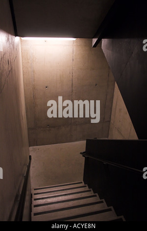 An internal undecorated urban stairwell, looking down one flight towards a 'landing', lit by only one single light - Stock Photo