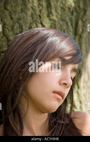Portrait of Teenage Girl Resting against Tree Trunk - Stock Photo
