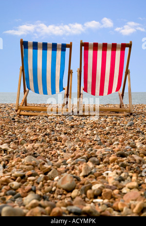 Two deckchairs on a pebble beach low perspective