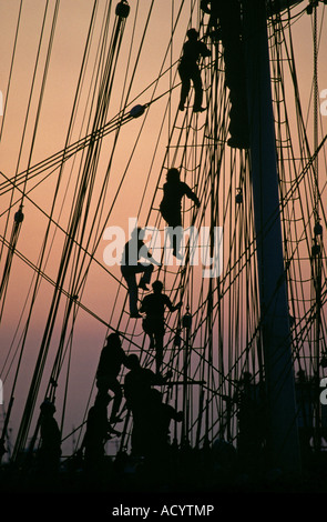 Sailors climb the rigging at sunset on the square rigged sailing ship Elissa as she sails out of Galveston Texas - Stock Photo