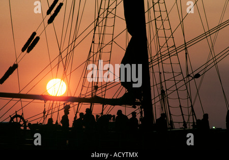 A bright Texas sunset through the rigging of the square rigged sailing ship Elissa as she sails out of Galveston - Stock Photo