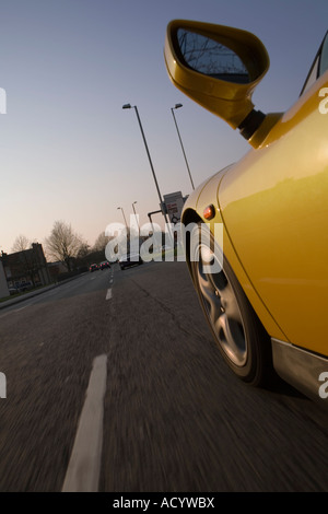 yellow sports car going down a street - Stock Photo