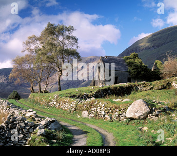 abandoned old cottage sits forlorn under irelands highest mountain - Stock Photo