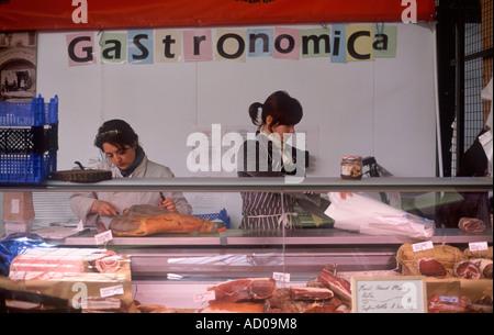 Prosciutto crudo, pancetta and speck — woman slicing dried ham behind counter of Italian delicatessen at Borough - Stock Photo