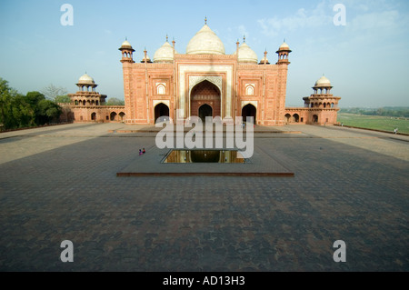Horizontal wide angle of the red sandstone Masjid mosque, part of the Taj Mahal complex on a bright sunny day - Stock Photo