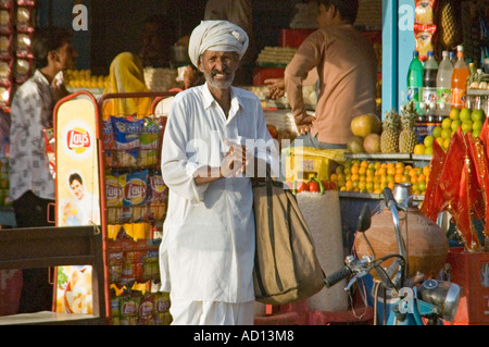 Horizontal view of an elderly Indian man buying snacks at a stall outside Karni Mata Temple 'Rat Temple' at Deshnoke - Stock Photo
