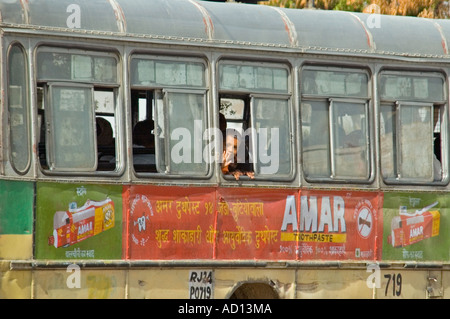 Horizontal view of a small Indian boy waving from the window of a rickety old public bus in central Delhi. - Stock Photo