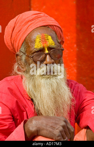 Vertical close up portrait of an elderly Sadhu in bright red clothing and turban sitting outside a temple - Stock Photo