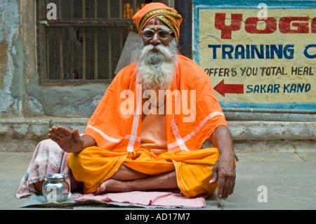 Horizontal portrait of an elderly Sadhu dressed in traditional saffron clothing sitting cross-legged on a pavement. - Stock Photo