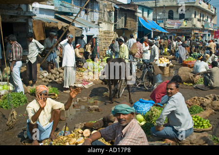 Horizontal wide angle of a typical busy Indian market with locals selling fruit and vegetables along the road - Stock Photo