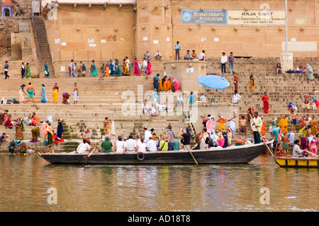 Wide angle view of people on the Raja Ghat performing their daily ritual with a tourist boat in the foreground. - Stock Photo