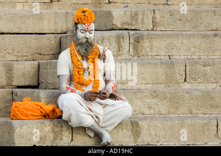 A sadhu (holyman) decorated with orange flower garlands sits in prayer at one of the ghats in Varanasi. - Stock Photo