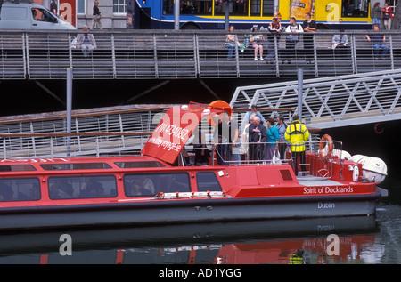 Passengers entering excursion ship on river Liffey in Dublin Ireland - Stock Photo