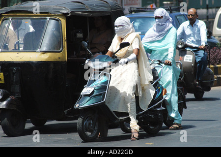 ASB73158 Two wheeler motor bike riders cover faces with scarfs to avoid summer heat and pollution at Nagpur Maharashtra - Stock Photo