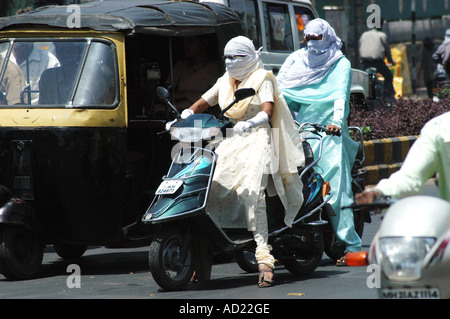 ASB73159 Two wheeler motor bike riders cover their faces with scarfs to avoid summer heat at Nagpur Maharashtra - Stock Photo