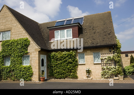 Three modern solar thermal panels with evacuated tubes on roof of detached house Cotswolds UK - Stock Photo
