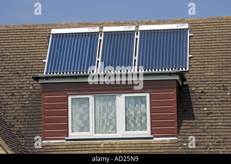 Three modern solar thermal evacuated tube panels on roof of detached house Cotswolds UK - Stock Photo