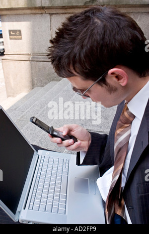 Young businessman uses mobile phone while working on his laptop in the City of London - Stock Photo