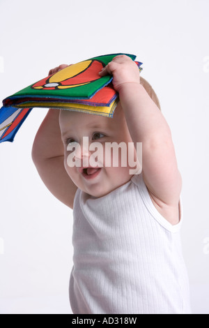 Little baby making fun with a textile toy book on his head - Stock Photo