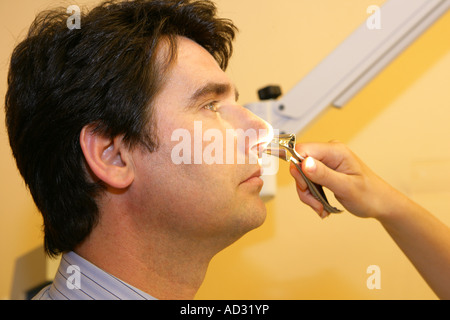 ENT Doctor examining a man s nose - Stock Photo