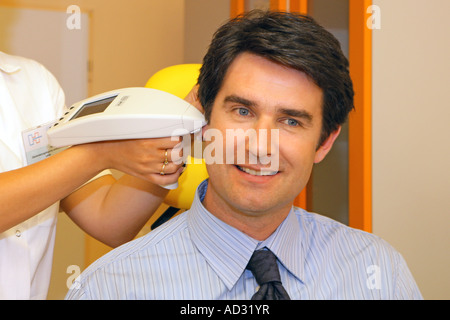 ENT Doctor examining a man s ear with an otoscope - Stock Photo