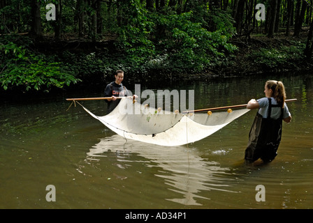 Teenage boy and girl using seine net to sample catch river fish - Stock Photo