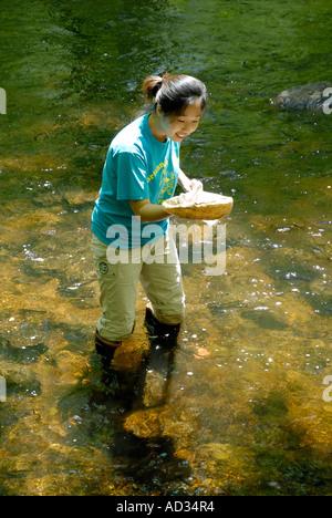 Asian teenage girl using net sampling river water for fish and invertebrate biological indicators of water quality - Stock Photo