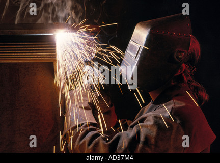 Man welding in mask on construction site. - Stock Photo