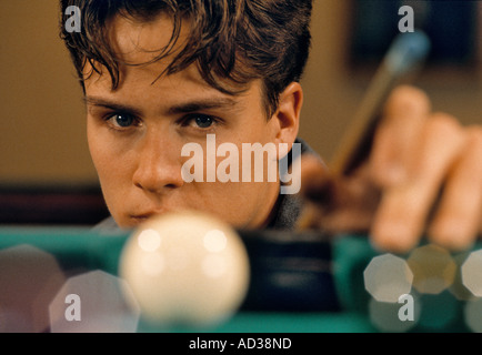 Young man playing pool. - Stock Photo